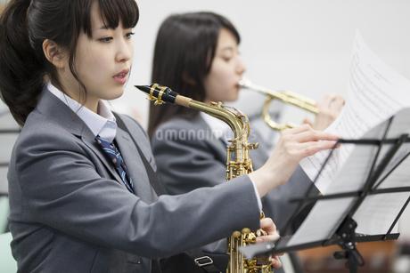 音楽室で楽譜をめくる女子学生の写真素材 [FYI02967498]