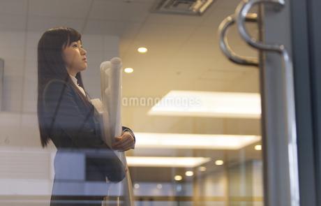 封筒と筒を持って上を向くビジネス女性の写真素材 [FYI02967501]