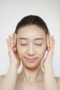 頬に両手を添えて目を瞑る女性の写真素材 [FYI02967502]