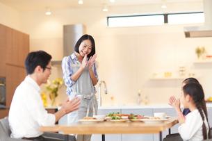 食事を囲み拍手する親子の写真素材 [FYI02967505]