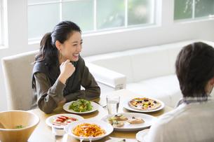 ダイニングテーブルで食事を楽しむ男性と女性の写真素材 [FYI02967512]