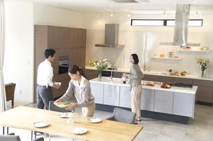 キッチンからテーブルに食事を運ぶ男女3人の写真素材 [FYI02967520]