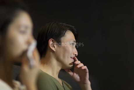 映画館で涙をこぼす男性の写真素材 [FYI02967523]