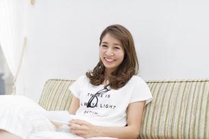 ソファに座って手紙を持って微笑む女性の写真素材 [FYI02967524]