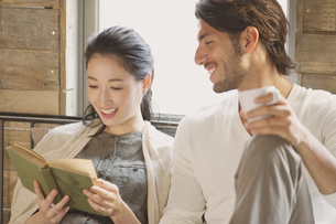 ベッドの上で本を読みながら笑い合う男性と女性の写真素材 [FYI02967525]