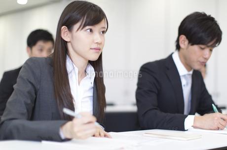 メモをとりながら講義を聴くビジネス男女の写真素材 [FYI02967527]