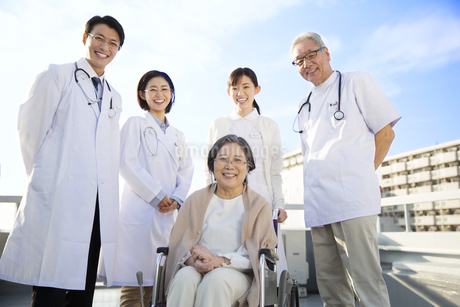 屋上で車椅子の患者に添う医師たちの写真素材 [FYI02967530]