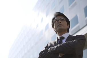 ビルの前で腕組みをするビジネス男性の写真素材 [FYI02967531]
