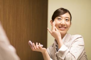 鏡に向かってメイクをする女性の写真素材 [FYI02967534]