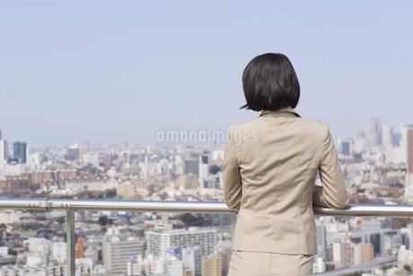 屋上でビル群を眺めるビジネス女性の後ろ姿の写真素材 [FYI02967535]