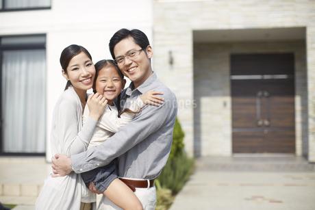 家の前に立つ3人家族の写真素材 [FYI02967539]