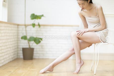 脚の太腿をマッサージをする女性の写真素材 [FYI02967540]