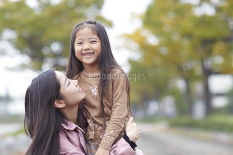 遊歩道で母に抱かれて微笑む女の子の写真素材 [FYI02967543]