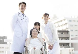 屋上で車椅子の患者に添う医師と看護師と女の子の写真素材 [FYI02967548]