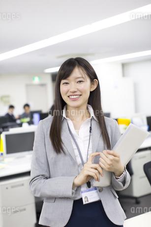 オフィスで立って微笑むビジネス女性の写真素材 [FYI02967550]