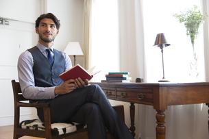ソファーに座り本を持って微笑むビジネス男性の写真素材 [FYI02967551]