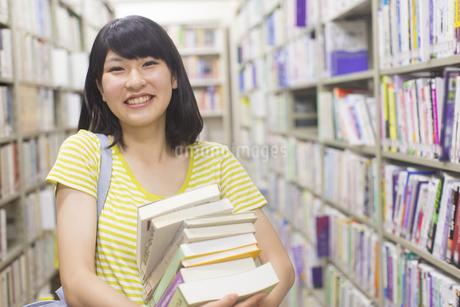 図書室で重ねた本を持って笑う女子学生の写真素材 [FYI02967555]