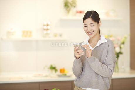 キッチンでスマートフォンを操作する女性の写真素材 [FYI02967559]