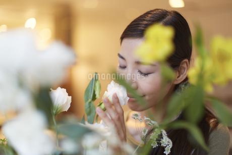 花の香りをかぐ女性の写真素材 [FYI02967560]