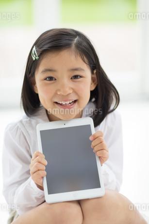 タブレットPCを手にして微笑む女の子の写真素材 [FYI02967568]