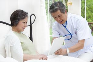 ベットのシニア女性にタブレットPCで説明する医者の写真素材 [FYI02967572]