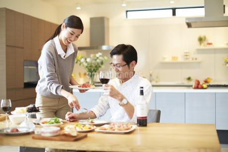 食事を配る女性とワインを手に微笑む男性の写真素材 [FYI02967573]