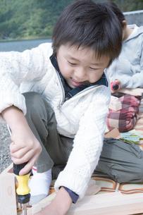 湖畔で木の工作をする男の子の写真素材 [FYI02967575]