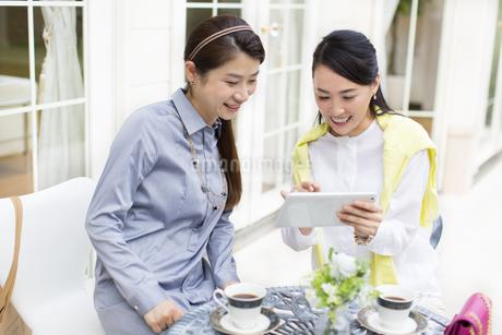 カフェのテーブルでタブレットPCを見る2人の女性の写真素材 [FYI02967576]