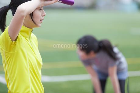 バトンをもって手で汗を拭っている女子学生の横顔の写真素材 [FYI02967577]