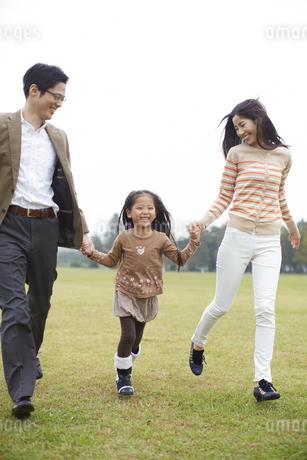 公園で手を繋いで駆ける家族の写真素材 [FYI02967578]