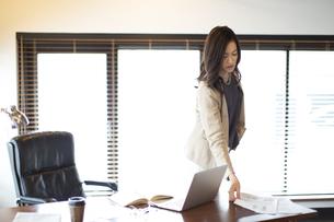 オフィスのデスクに資料を置くビジネス女性の写真素材 [FYI02967579]