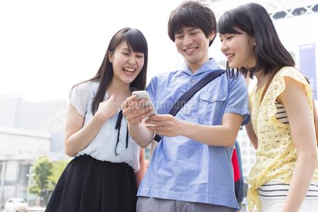 街中でスマートフォンを見て微笑む3人の若者の写真素材 [FYI02967580]