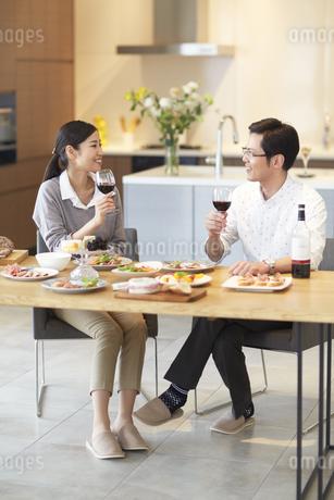テーブルでワインを手に会話する男女の写真素材 [FYI02967581]