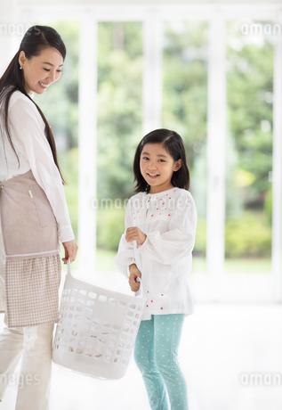 洗濯カゴを持って微笑む母と娘の写真素材 [FYI02967585]
