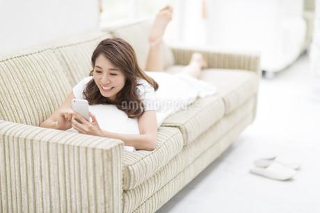 ソファの上でスマートフォンを見る女性の写真素材 [FYI02967587]