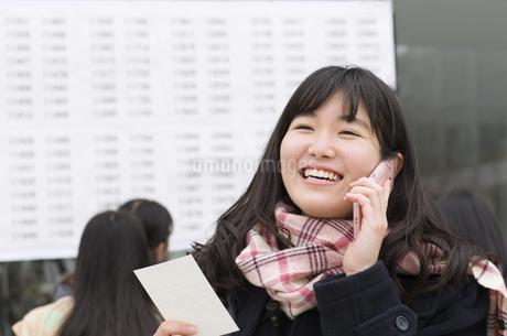 合格発表を喜び電話をする女子高校生の写真素材 [FYI02967595]