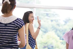 教室で手を振る女子学生の写真素材 [FYI02967597]