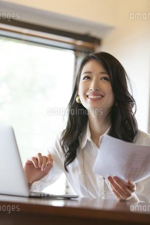 オフィスで資料を手に持ち微笑むビジネス女性の写真素材 [FYI02967598]