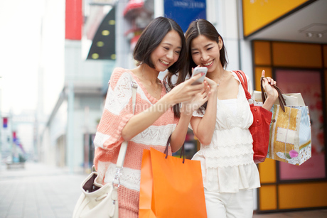 買い物中にスマートホンを見て笑う女性二人の写真素材 [FYI02967599]