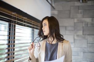 オフィスで資料と眼鏡を手に持ち遠くを眺めるビジネス女性の写真素材 [FYI02967600]