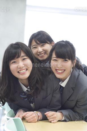 教室の机の上で重なって笑う女子高校生たちの写真素材 [FYI02967608]