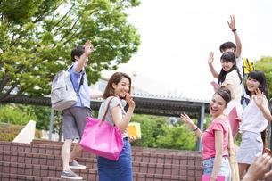 キャンパスで振り向きながら手を上げる学生たちの写真素材 [FYI02967609]