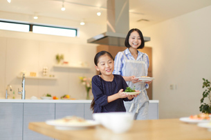 テーブルに食事を用意する親子の写真素材 [FYI02967612]