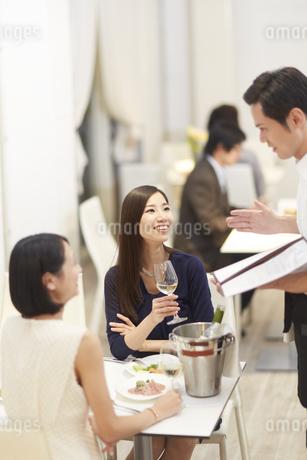 レストランで店員の話を聞く女性二人の写真素材 [FYI02967616]