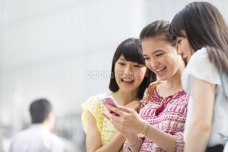 スマートフォンを見つめて喜ぶ3人の若い女性の写真素材 [FYI02967618]