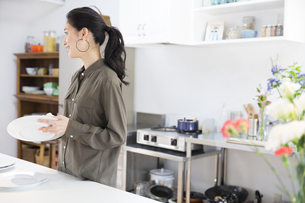 キッチンで食器を拭く女性の写真素材 [FYI02967620]