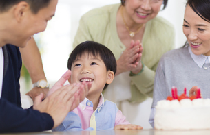 ケーキを前に誕生日のお祝いをする家族の写真素材 [FYI02967622]