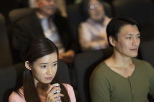 映画館で涙をこぼす女性の写真素材 [FYI02967624]