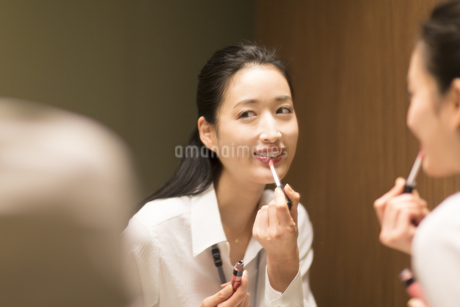 鏡に向かってメイクをする女性の写真素材 [FYI02967625]