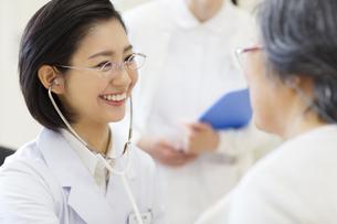 患者に聴診器をあてる女性医師の写真素材 [FYI02967630]